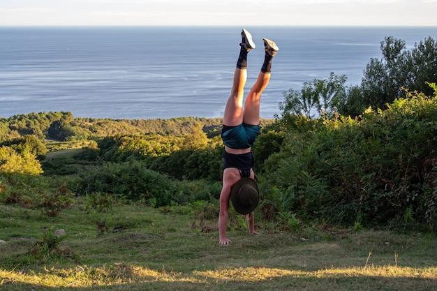 Молодая девушка делает стойку на руках на зеленом холме с морем