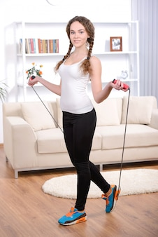 Young girl doing exercises with skipping rope at home