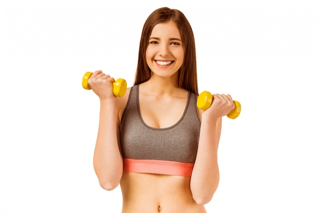 Young girl doing fitness exercises with dumbbells.