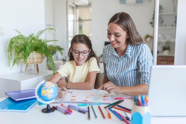 Молодая девушка делает домашнее задание в школе со своей матерью, дома, она пишет в книге. дочь матери и ребенка делает домашнее задание, писать и читать дома