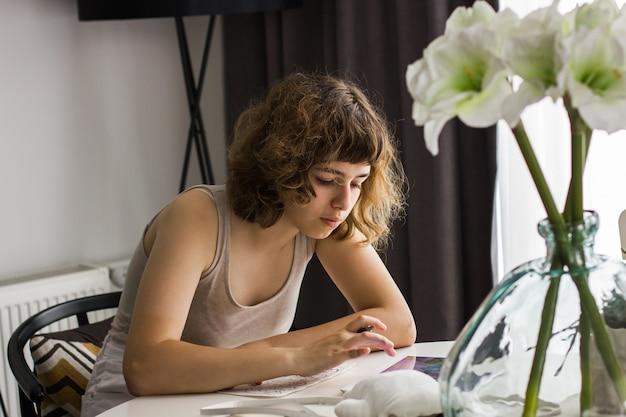 흰색 테이블에서 숙제를 하는 어린 소녀. 가정 교육 및 홈스쿨링