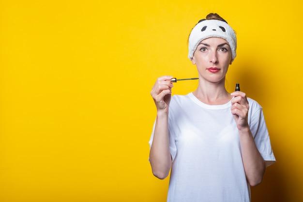 화장을 하 고 어린 소녀입니다. 그의 손에 마스카라를 들고 그의 머리에 흰색 티셔츠와 붕대를 착용