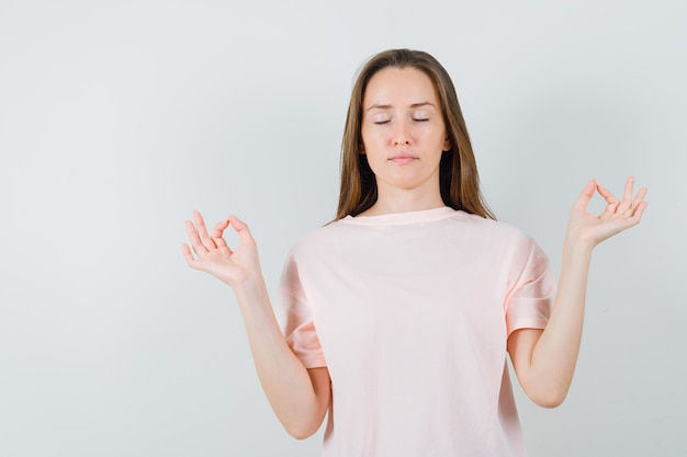 Ragazza che fa meditazione con gli occhi chiusi in maglietta rosa e che sembra calma. vista frontale.