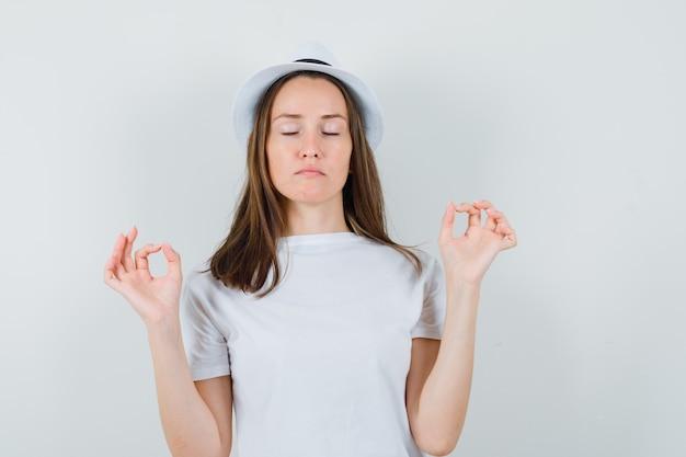 Ragazza che fa meditazione con gli occhi chiusi in maglietta bianca, cappello e guardando rilassato, vista frontale.