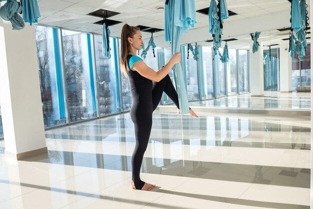 Молодая девушка делает утреннюю зарядку, используя летательную йогу и растягивается в фитнес-тренировке