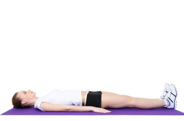 Молодая девушка делает физические упражнения на полу