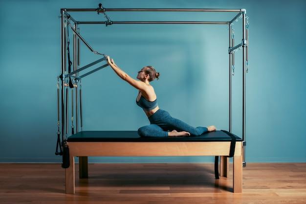 개혁 침대와 필라테스 운동을하는 어린 소녀. 개혁자 회색 배경, 낮은 키, 예술 빛에 아름다운 슬림 피트니스 트레이너. 피트니스 개념.