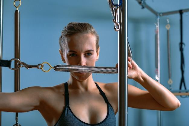 Молодая девушка делает упражнения пилатес на кровати реформатора. красивый тонкий фитнес-тренер на сером фоне реформатора, сдержанный, свет искусства. концепция фитнеса.