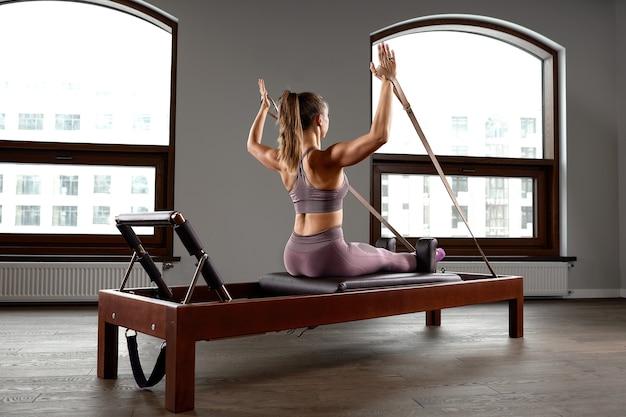 리포머 침대에서 필라테스 운동을 하는 어린 소녀. 개혁자 회색 배경, 낮은 키, 예술 조명에 아름다운 슬림 피트니스 트레이너. 피트니스 개념입니다.