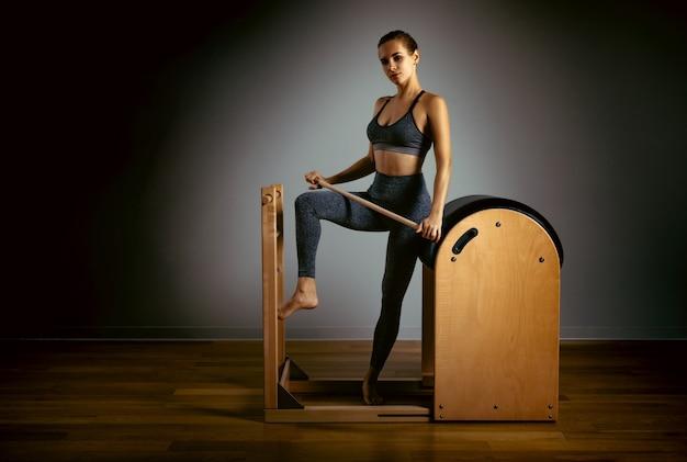 改質ベッドでピラティス運動をしている若い女の子。リフォーマーグレースペース、ローキー、アートライトの美しいスリムフィットネストレーナー。フィットネスのコンセプト