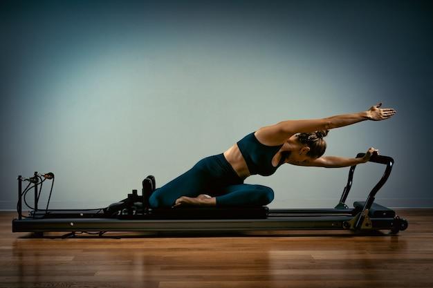 Молодая девушка делает упражнения пилатес на кровати-реформаторе