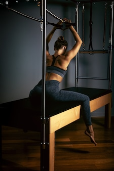 Young girl doing pilates exercises with a reformer bed. beautiful slim fitness trainer on reformer gray space, low key, art light. fitness concept