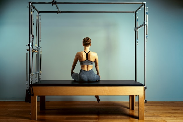Young girl doing pilates exercises with a reformer bed.