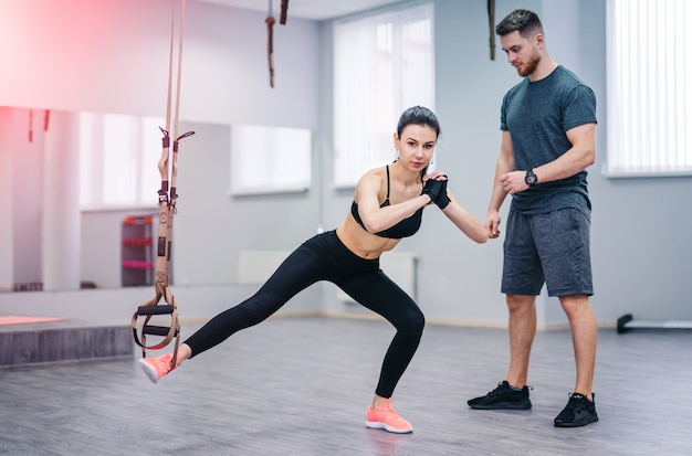 Young girl doing suspension rope exercise together with her personal coach on the gym background.