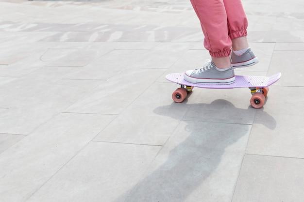 Молодая девушка делает трюки с ее скейтборд крупным планом