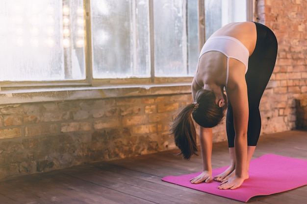 Young girl doing yoga alone in the yoga room near the window