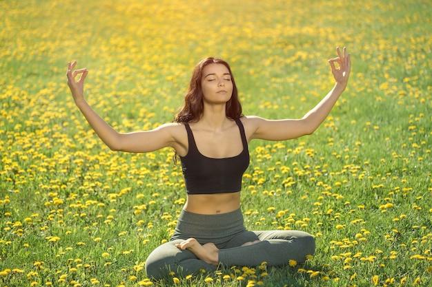 公園でヨガをしている少女。屋外で蓮華座を行うヨガを練習している女性