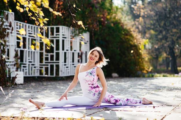 Молодая девушка занимается йогой в парке