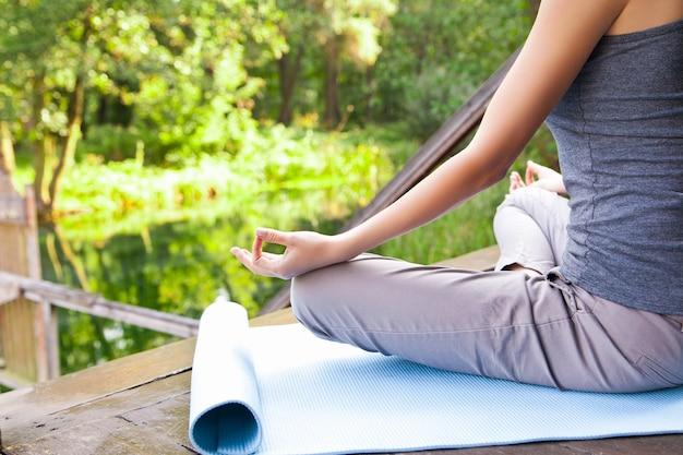公園でヨガの蓮華座ポーズをしている少女