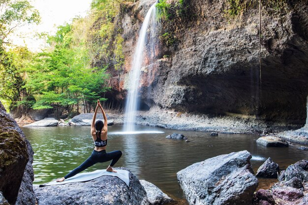 Молодая девушка занимается йогой возле водопада