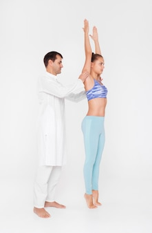 Young girl doing yoga with trainer, yoga class paired with the coach.