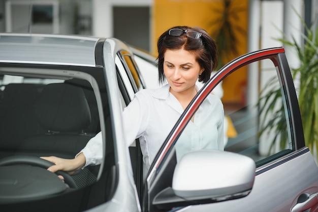 クレジットでさらに購入するために、自動車販売店で新しい白い車を検査する新しい車を夢見ていた若い女の子