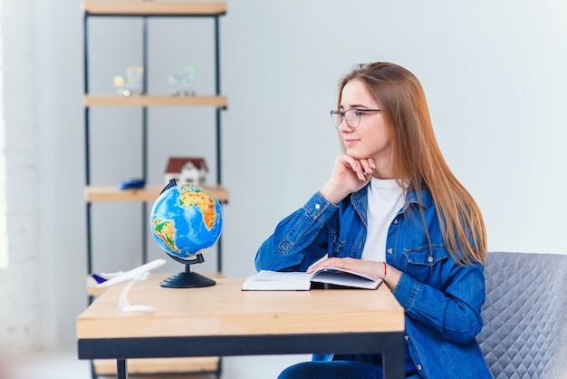 Young girl dreams about vacations while studying at white living room. studying geography with globe. cute schoolgirl in denim clothes makes homework.