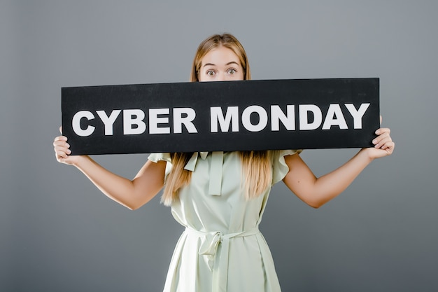 Young girl in dress covers her mouth with cyber monday sign isolated over grey