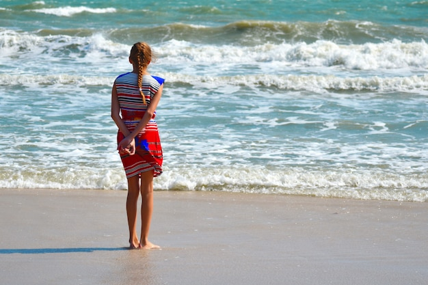 A young girl in a dress looks at the sea.