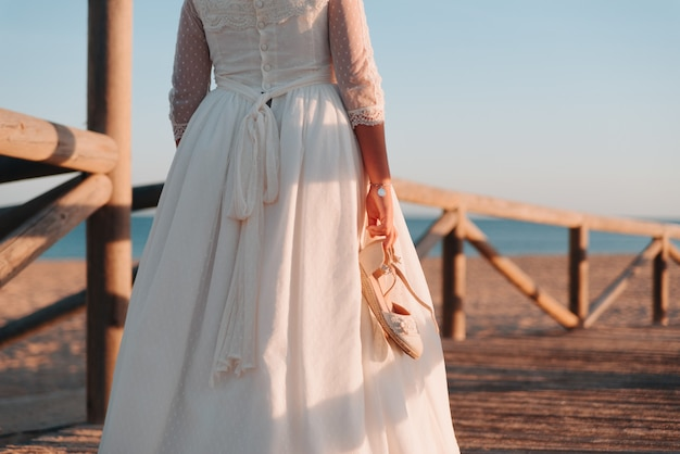 Young girl in a dress walking with her shoes in hand on a wooden breakwater
