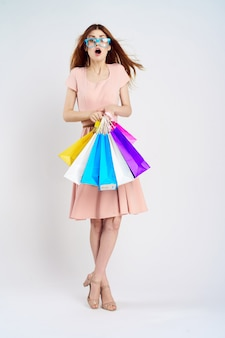 Young girl in a dress with shopping bags in hands on a light wall, shopaholic