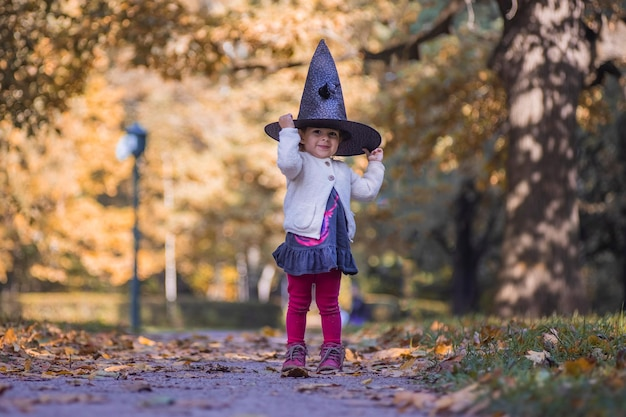 A young girl dressed in black as a witch with hat