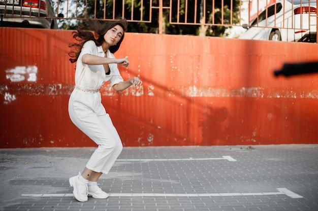 흰 셔츠를 입은 어린 소녀가 화창한 날 페인트로 칠해진 콘크리트 벽에 기대어 거리에서 현대 무용을 추고 있습니다.