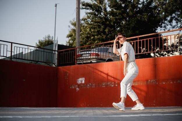 흰 셔츠를 입은 어린 소녀가 화창한 날 주차장을 배경으로 거리에서 현대 무용을 추고 있습니다.