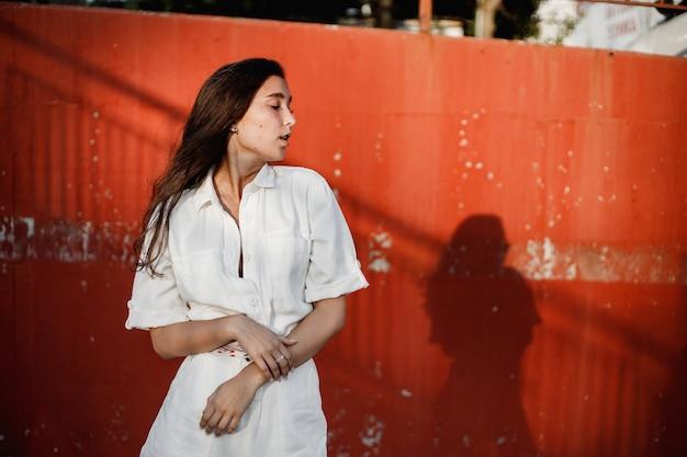 흰 셔츠를 입은 어린 소녀가 화창한 날 페인트로 칠해진 콘크리트 벽을 따라 거리에서 포즈를 취합니다.