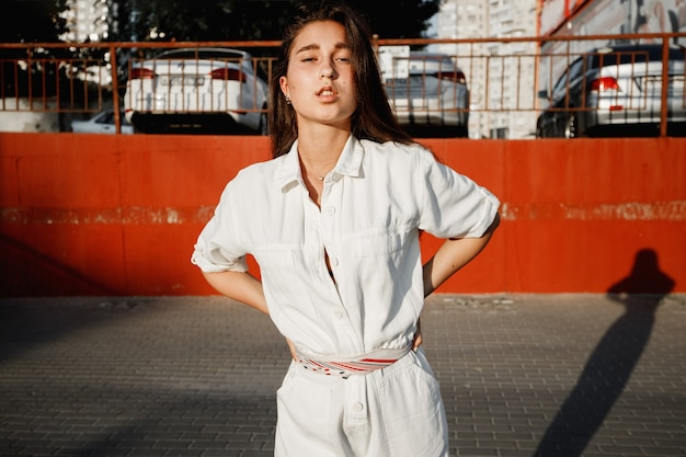 흰 셔츠를 입은 어린 소녀가 화창한 날 주차장을 배경으로 거리에서 포즈를 취하고 있습니다.