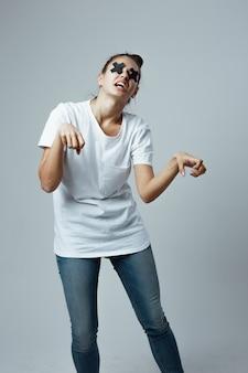 白いtシャツとジーンズに身を包んだ少女が、ゾンビのようにスタジオの白い背景に立っています。