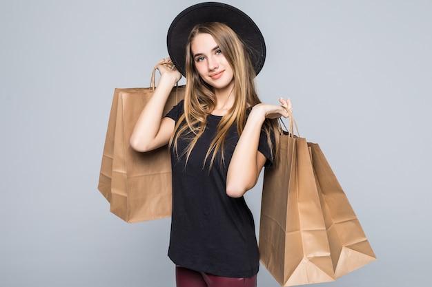Молодая девушка, одетая в черную футболку и кожаные брюки, держит пустые ремесленные хозяйственные сумки с ручками, изолированными на белом