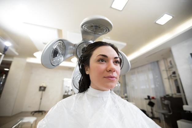 어린 소녀는 전문 헤어 드라이어로 미용사에서 머리카락을 말립니다. 이발소에서 젊은 여자의 초상화