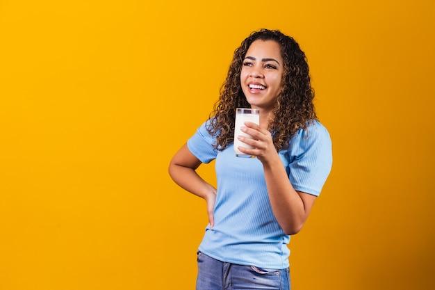 テキストのためのスペースで背景にミルクのガラスを飲む若い女の子。
