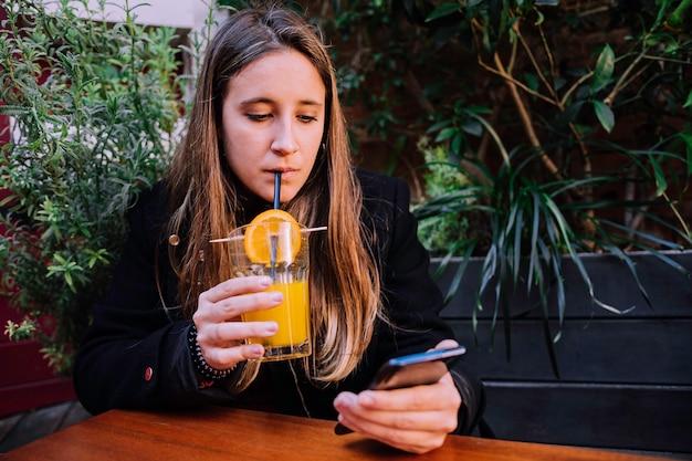 Молодая девушка пьет натуральный коктейль на террасе и смотрит на мобильный