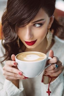 유행 카페에서 커피를 마시는 어린 소녀