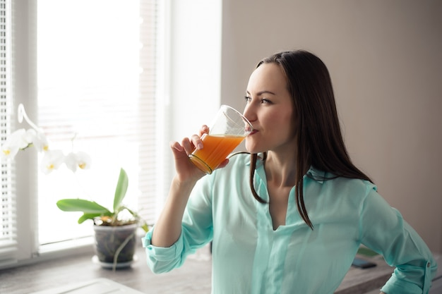 Young girl drinking from a glass glass cup of orange juice at the window in the kitchen