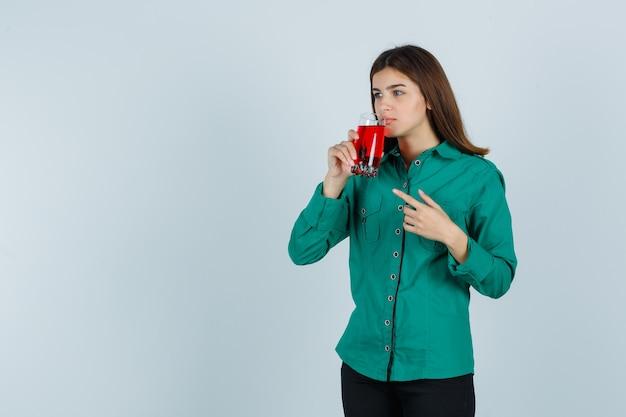 Молодая девушка пьет стакан красной жидкости, указывая на нее указательным пальцем в зеленой блузке, черных штанах и смотрит сосредоточенно. передний план.
