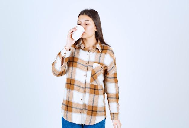 흰 벽에 플라스틱 컵을 마시는 어린 소녀.