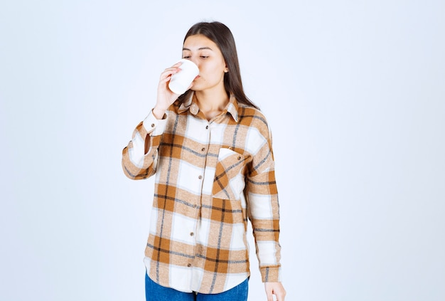 Young girl drinking plastic cup of tea on white wall.
