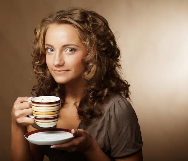 Young girl drinking tea or coffee
