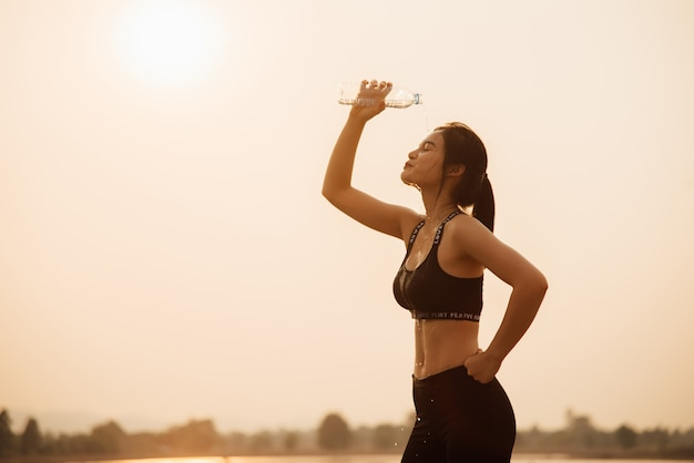 Young girl drinking water during in the jogging