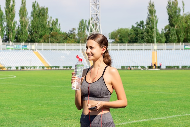Young girl drinking water from bottle after running at stadium.
