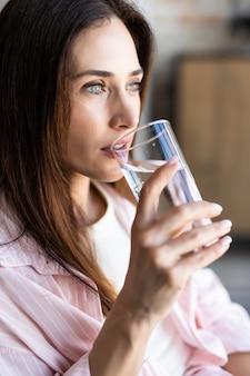 Молодая девушка питьевой воды, сидя на диване у себя дома и глядя на камеру